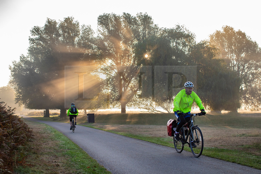 © Licensed to London News Pictures. 10/10/2018. London, UK. Cyclists at sunrise in Bushy Park, south London. Forecasters are expecting unusually warm temperatures for October. Photo credit: Rob Pinney/LNP