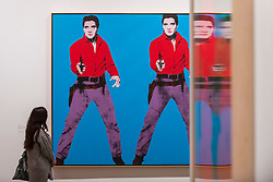 "© Licensed to London News Pictures. 10/03/2020. LONDON, UK. A staff member views a reflected ""Elvis I and II"", 1963-4, by Andy Warhol. Preview of ""Andy Warhol"", a retrospective of over 100 works by one of the most recognisable artists of the late 20th century.  The exhibition runs 12 March to 6 September 2020 at Tate Modern.  Photo credit: Stephen Chung/LNP"