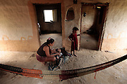 A woman comforts her 9 month old lying in crib made from a car tire in her simple home in Agua Catilho, Honduras.  Honduras is considered the third poorest country in the Western Hemisphere (Haiti, Nicaragua). With over 50% of the population living below the poverty line and 28% unemployed, Hondurans frequently turn to illegal immigration as a solution to their desperate situation. The Department of Homeland Security has noted an 95% increase in illegal immigrants coming from Honduras between 2000 and 2009, the largest increase of any country.