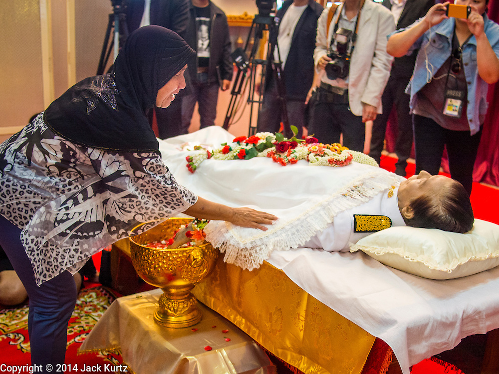 12 OCTOBER 2104 - BANG BUA THONG, NONTHABURI, THAILAND:  A Thai Muslim woman pays respects to  Apiwan Wiriyachai on the first day of his funeral rites at Wat Bang Phai in Bang Bua Thong, a Bangkok suburb, Sunday. Apiwan was a prominent Red Shirt leader, member of the Pheu Thai Party of former Prime Minister Yingluck Shinawatra, and a member of the Thai parliament. The military government that deposed the elected government in May, 2014, charged Apiwan with Lese Majeste for allegedly insulting the Thai Monarchy. Rather than face the charges, Apiwan fled Thailand to the Philippines. He died of a lung infection in the Philippines on Oct. 6. The military government gave his family permission to bring him back to Thailand for the funeral. He will be cremated later in October. The first day of the funeral rites Sunday drew tens of thousands of Red Shirts and their supporters, in the first Red Shirt gathering since the coup.   PHOTO BY JACK KURTZ
