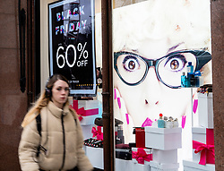 Edinburgh, Scotland, UK. 23 November, 2018. Shoppers walk past shops with Black Friday price discount promotion displays on Princes Street , Edinburgh, Scotland,