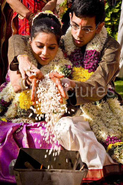 At a Hindu wedding ceremony, bride Shweta Singhal and groom Rohit clasp each others hands with a handful of puffed rice which is then thrown into a fire as an offering to the god of fire, Agni. Neemrana Fort Palace, Rajasthan, India