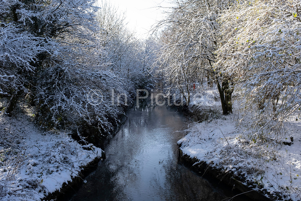 Winter scene in the snow on the River Rea in Canon Hill Park in Moor Green on 25th January 2021 in Birmingham, United Kingdom. Deep snow arrived in the Midlands giving some light relief and fun during the current lockdown for people who simply enjoyed the weather.