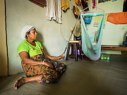 02 JUNE 2015 - KULAI, JOHORE, MALAYSIA:  A Rohingya woman rocks MOHAMMAD SHIDE, 6 years old, in a crib. The woman helps take care of the boy when his mother is at work. The child was born healthy but developed symptoms similar to polio before they came to Malaysia from Myanmar. Now his mother can't afford a proper medical diagnosis and his condition is worsening. He is blind and losing control of his muscular system. His mother doesn't know what is wrong with him but earns less than $6 US per day selling used books on the street and can't afford medical care. The UN says the Rohingya, a Muslim minority in western Myanmar, are the most persecuted ethnic minority in the world. The government of Myanmar insists the Rohingya are illegal immigrants from Bangladesh and has refused to grant them citizenship. Most of the Rohingya in Myanmar have been confined to Internal Displaced Persons camp in Rakhine state, bordering Bangladesh. Thousands of Rohingya have fled Myanmar and settled in Malaysia. Most fled on small fishing trawlers. There are about 1,500 Rohingya in the town of Kulai, in the Malaysian state of Johore. Only about 500 of them have been granted official refugee status by the UN High Commissioner for Refugees. The rest live under the radar, relying on gifts from their community and taking menial jobs to make ends meet. They face harassment from Malaysian police who, the Rohingya say, extort bribes from them.    PHOTO BY JACK KURTZ