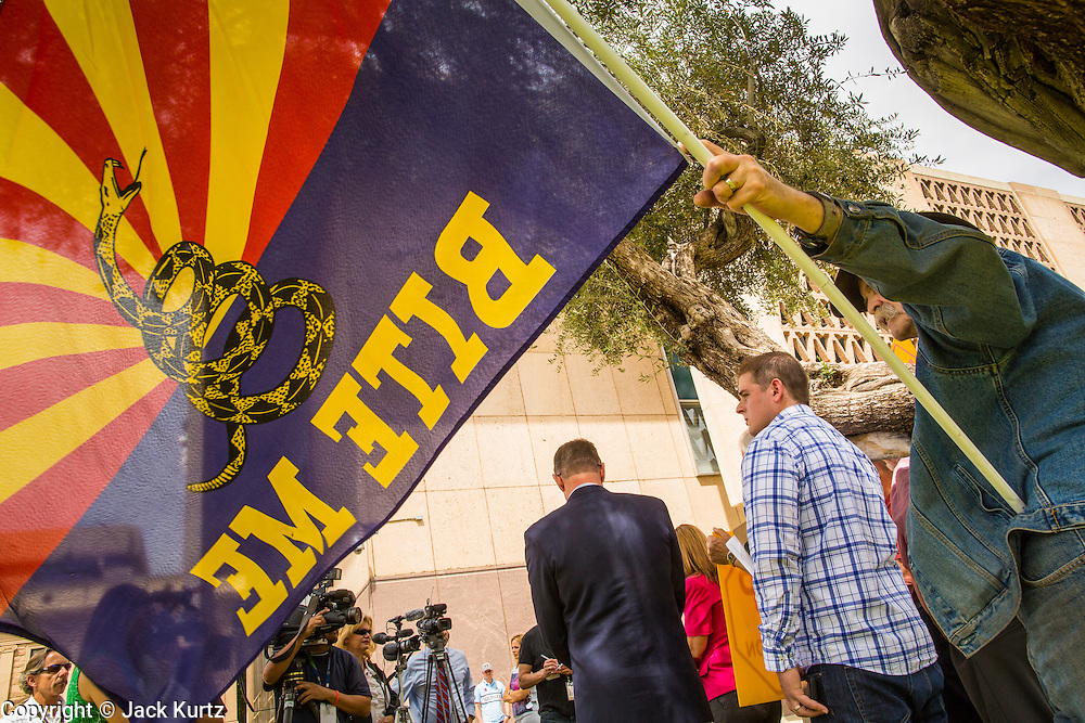 25 APRIL 2012 - PHOENIX, AZ: MIKE KEATING, a member of the Tea Party, frames the media and Tea Party members during a Tea Party press conference about illegal immigration in front of the Arizona state capitol Wednesday. Immigrants' rights groups opposed to SB1070 and Tea Party affiliated groups that support SB1070 gathered at the state capitol in Phoenix Wednesday to express their opposition and support of the bill. SB1070 was signed by Arizona Governor Jan Brewer in April 2010. At the time it was the toughest anti-illegal immigration bill in the country. Immigrants' rights groups sued Arizona and the federal courts stopped enforcement of the bill. The bill ended up in the US Supreme Court which heard arguments Wednesday. A ruling on the bill is expected in June.   PHOTO BY JACK KURTZ