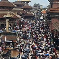 NEPAL, Kathmandu Valley.  Beset by a monsoon rain squall, Hindus celebrate Krishna's Birthday (Krishna Asthami) at at temples and pagodas in Durbar Square in Patan.