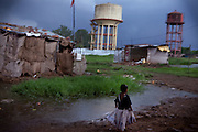 A young girl is running under the rain in the impoverished Oriya Basti Colony, Bhopal, Madhya Pradesh, India, near the abandoned Union Carbide (now DOW Chemical) industrial complex. Copyright: Alex Masi / Focus For Humanity