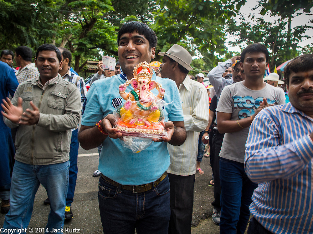 31 AUGUST 2014 - SARIKA, NAKHON NAYOK, THAILAND: A man carries a statue of Ganesh to a river where statues of Ganesh will be submerged at Shri Utthayan Ganesha Temple in Sarika, Nakhon Nayok. Ganesh Chaturthi, also known as Vinayaka Chaturthi, is a Hindu festival dedicated to Lord Ganesh. It is a 10-day festival marking the birthday of Ganesh, who is widely worshiped for his auspicious beginnings. Ganesh is the patron of arts and sciences, the deity of intellect and wisdom -- identified by his elephant head. The holiday is celebrated for 10 days, in 2014, most Hindu temples will submerge their Ganesh shrines and deities on September 7. Wat Utthaya Ganesh in Nakhon Nayok province, is a Buddhist temple that venerates Ganesh, who is popular with Thai Buddhists. The temple draws both Buddhists and Hindus and celebrates the Ganesh holiday a week ahead of most other places.    PHOTO BY JACK KURTZ