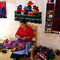 South America, Ecuador, Peguche.  A weaver's wife in Peguche embroiders textiles for selling at the Otavalo Market.