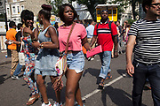The 49th Notting Hill Carnival in West London. A celebration of West Indian / Caribbean culture and Europe's largest street party, festival and parade. Revellers come in their hundreds of thousands to have fun, dance, drink and let go in the brilliant atmosphere. Girl with matching pink t-shirt and purse.