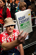 London, UK. Thursday 16th August 2012. Supporters of Julian Assange outside the Ecuador Embassy. One holding up a book (Hopes and Prostects) by celebrated author Noam Chomski.