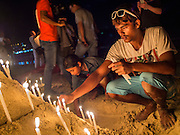 26 DECEMBER 2014 - PATONG, PHUKET, THAILAND: A Thai man lights candles for victims of the 2004 tsunami on Patong Beach in Patong, Phuket. Hundreds of people died in Patong and nearly 5400 people died on Thailand's Andaman during the 2004 Indian Ocean Tsunami that was spawned by an undersea earthquake off the Indonesian coast on Dec 26, 2004. In Thailand, many of the dead were tourists from Europe. More than 250,000 people were killed throughout the region, from Thailand to Kenya. There are memorial services across the Thai Andaman coast this weekend.    PHOTO BY JACK KURTZ