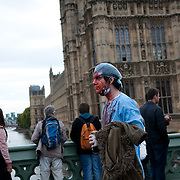 A protestor walking back over Westminster Bridge after having been denied leaving the bridge from the North side. The bridge is now a mix of protestors and passers-by..The Health and Care Bill has been passed by Parliament and is due to go to the House of Lords. In protest against the bill which aim to deconstruct and privatise large parts of the NHS UK Uncut activists together with health workers and trade unionists blocked the Westminster Bridge from 1pm til 5.30pm.