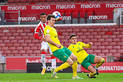 Stoke City's Tom Ince crosses, challenged by Max Aarons  and Christoph Zimmermann of Norwich City - Mandatory by-line: Nick Browning/JMP - 24/11/2020 - FOOTBALL - Bet365 Stadium - Stoke-on-Trent, England - Stoke City v Norwich City - Sky Bet Championship