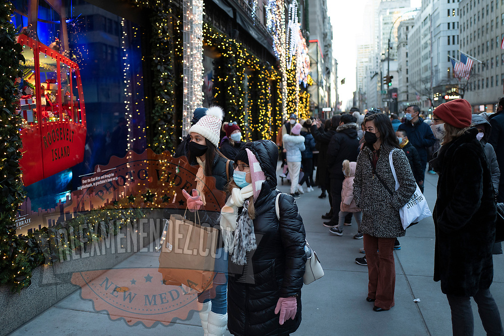 Masked shoppers and visitors walk down 5th Avenue and stop to look at the Saks 5th Avenue window displays for the Holiday season during the Coronavirus (Covid-19) outbreak in Manhattan,New York on Sunday, December 6, 2020. (Alex Menendez via AP)