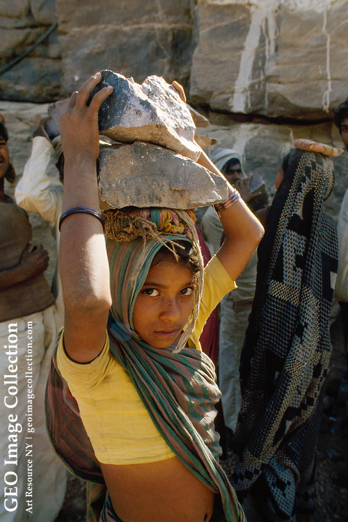 """Women construction workers load trucks by hand with rocks from what will be the diversion tunnel of the Narmada Sagar Dam.  According to the photographer, the Narmada Sagar dam site is in a seismic area, which raises questions with oppon ents of the dam.  On April 23, 1990, the NGS Control Center killed the Narmada River articl e proposed by Royina Grewal.  The story was put on a back burner after Indian e nvironmental groups began to protest the construction of two giant reservoirs, """"the Sardar Sarovar in Gujarat and the Narmada Sagar in Madhya Pradesh, which between them would hold more water than any other dam on the Indian sub-continent."""" Thus, th e future of the Narmada River Development program could not be ascertained.  Ac cording to Grewal , the Narmada Development Authority proposes to construct """"nearly 160 ma jor and medium hydroelectric and irrigation schemes that would irrevocably alte r the flow of the river and the lives it sustains."""" In a 2/20/90 letter to NGS Sr. Editor John Putman, Sardar F PHOTO GRAPH:  2/9/88."""