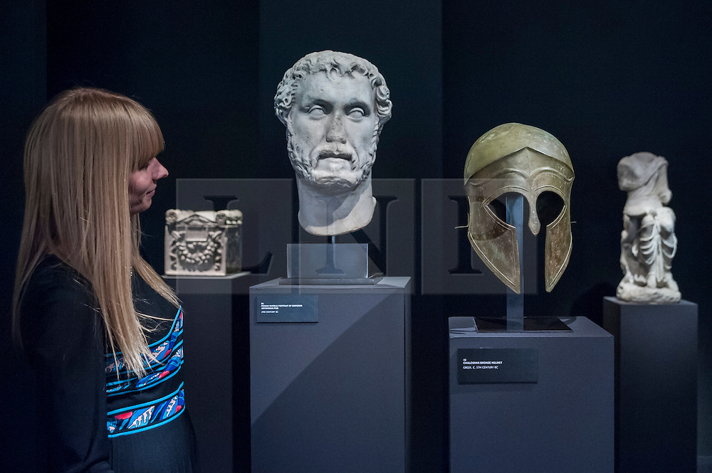 © Licensed to London News Pictures. 24/06/2015. London, UK.   A visitor looks at (L) a Roman Portrait of Antoninus Pius, 2nd century B.C. and (R) a Greek chalcidian bronze helmet, 5th century B.C., at the preview of Masterpiece London, the international cross-collecting Fair for art, antiques and design which takes place at The Royal Hospital Chelsea 25 June to 1 July. Photo credit : Stephen Chung/LNP
