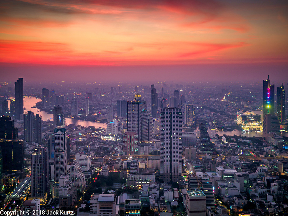 27 DECEMBER 2018 - BANGKOK, THAILAND:  Looking west at sunset from the rooftop observation deck of the King Power Maha Nakhon Tower. The Chao Phraya River is in the center of the frame. The MahaNakhon Skywalk, at the top of the King Power Maha Nakhon Tower, is 1,030 feet (314 meters) above street level. It is the tallest building and highest vantage point in Bangkok. The skywalk opened in November and has been drawing large crowds.     PHOTO BY JACK KURTZ