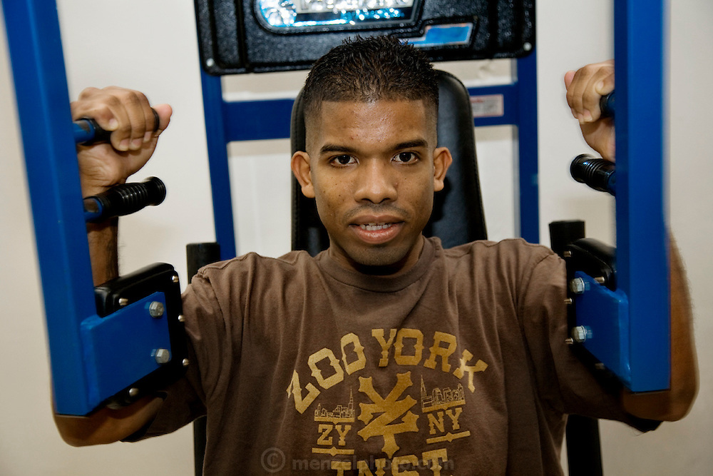 """Felipe Adams, a 30-year-old Iraq war veteran who was paralyzed by a sniper's bullet in Baghdad, Iraq, works on his upper body strength during a rehab session at the VA Long Beach Medical Center in Inglewood, California. (From the book What I Eat: Around the World in 80 Diets.) The caloric value of his day's worth of food on a day in the month of September was 2100 kcals. He is 30; 5'10"""" and 135 pounds. MODEL RELEASED."""
