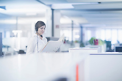 Businesswoman wearing headset and reading document in cubicle, Freiburg Im Breisgau, Baden-Württemberg, Germany
