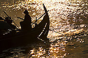 FISHERMEN MEKONG RIVER. South East Asia, Cambodia, Phnom Penh, Mekong River. The Cham fisher people live in various desolated villages along the banks of the Mekong and Tonle Sap rivers. The fisher families live like river gypsy nomads, working and living on their boats, sleeping under a sprung bamboo frame, all their worldly goods stored below deck. They live in extended families, with numerous boats, together for safety. Their diet is rice, vegetables and fish. Their sleek wooden boats are powered by petrol outboard motors with batteries or generators to supply lighting at night. Their fishing technique is laying nets twice or three times per day, which are weighted well below the surface, using old paint aerosal canisters as buoyant floaters, hanging just beneath the surface. These particular fisher families, living at the junction of the Mekong and Tonle Sap rivers, overlooked by Phnom Penh, sell their catch at the Vietnamese market, on the banks of the river. Their life and fortunes are controlled by the cycle of the river. As the river levels drop, so the quantity of fish decreases, until after the heavy floods of the monsoon they fill the river again. They are poor traditional Muslims, marginalised from mainstream society, living a third world life in the immmediate shadow of the first world. The Cham, originally a people of an ancient kingdom called Champa, are a small and disenfranchised community who were disinherited of their land. They are a socially important ethnic group in Cambodia, numbering close to 300,000. The Cham people, live in some 400 villages across Kampong Chnang and Kampong Cham provinces. Their religion is Muslim and their language belongs to the Malayo-Polynesian family. Their livelihoods are as diverse as rice farming, cattle trading, hunting and fishing.///A Cham fisherwoman steers her boat into shore, silhouetted against the golden waters of the Mekong river at sunset