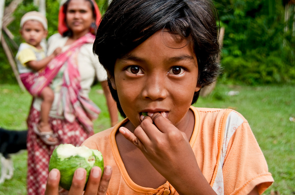 A young girl eating fruit in the Aceh region.