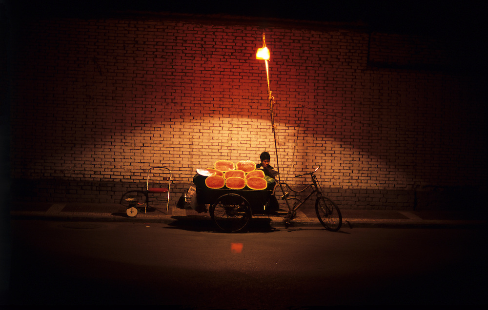 Illuminated by a single streetlight a man sits by the side of the road and waits for customers to sell them watermelons in the relative cool of the night in the old Muslim Quarter of Xian, Shaanxi province, central China.