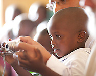 Kigal, Rwanda.Photo Randy Vanderveen.A young Rwandan boy takes a photo with a digital camera while seated on the lap of a visitor to a baptist church in Rwanda.