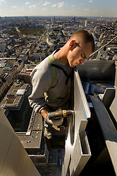 BRUSSELS, BELGIUM - APRIL-04-2007 -  An iron worker hangs high above the ground as he applies the exterior skin on a new 35 story skyscraper being built in downtown Brussels. (Photo  © Jock Fistick)