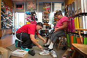 Store manager Mark Coutreras assists customer Yany Orona try on several pairs of shoes for work and break time dancing at Beck's Shoes in Milpitas, Calif., on Sept. 18, 2012.  Photo by Stan Olszewski/SOSKiphoto.
