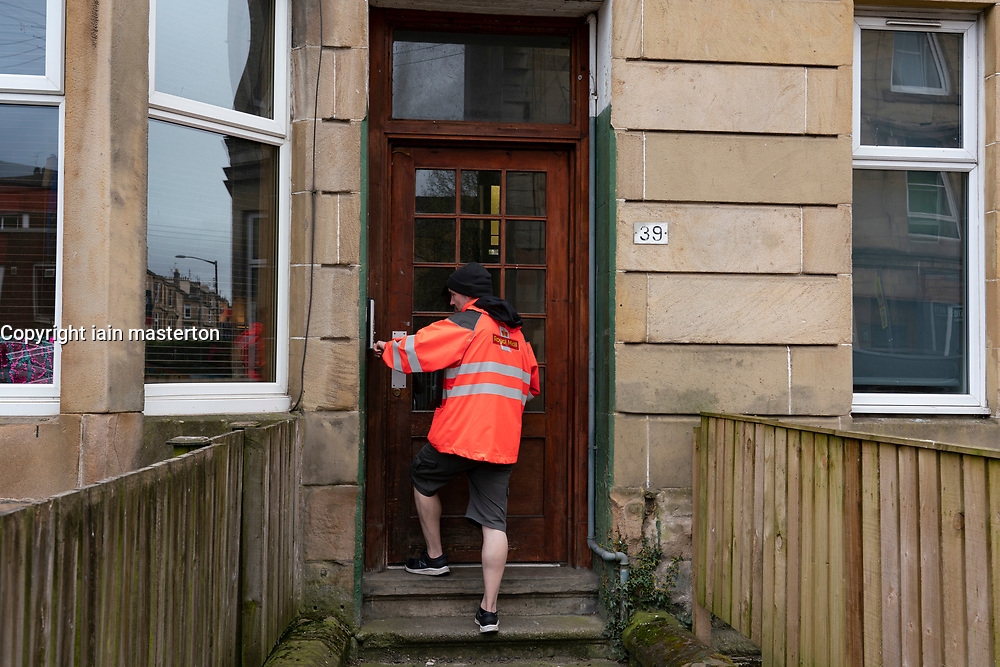 Glasgow, Scotland, UK. 3 April, 2020. Images from the south side of Glasgow at the end of the second week of Coronavirus lockdown. Pictured; Royal Mail postman making deliveries in Shawlands. Iain Masterton/Alamy Live News