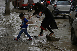 June 16, 2018 - Kathmandu, Nepal - A woman and child struggle to get across a muddy road caused after a heavy rainfall in Boudha, Kathmandu, Nepal on Saturday, June 16, 2018. (Credit Image: © Skanda Gautam via ZUMA Wire)
