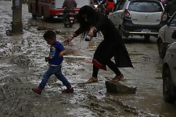 June 16, 2018 - Kathmandu, Nepal - A woman and child struggle to get across a muddy road caused after a heavy rainfall in Boudha, Kathmandu, Nepal on Saturday, June 16, 2018. (Credit Image: © Skanda Gautam via ZUMA Wire)