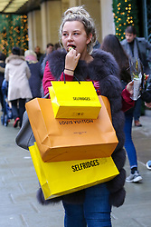 © Licensed to London News Pictures. 23/12/2018. London, UK. A woman with shopping bags outside Selfridges store on Oxford Street. Last minute Christmas shoppers take advantage of pre-Christmas bargains in London's Oxford Street. Fewer shoppers have been reported shopping in Britain's high streets as online sales increase. Photo credit: Dinendra Haria/LNP
