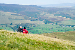 A couple enjoy the view from Mam Tor, one of Castleton's most famous landmarks. it has an active debris flow resulting from a rotational landslide that happened around 4,000 years ago and gives Mam Tor it's very distinctive eastern face. The area below this face is continually moving as the loose shale is undermined by natural erosion The A625 main road from Stockport to Sheffield used to run past the eastern Face of Mam Tor until 1974 when it was swept away by a landslide Finally closed for good in 1979. It's now only passable on foot. <br /> 11 October 2015<br />  Image © Paul David Drabble <br />  www.pauldaviddrabble.co.uk<br />  11 October 2015<br />   Image © Paul David Drabble <br />   www.pauldaviddrabble.co.uk