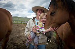 .Hilary Zaranek and her daughter Elle are met by  draft horses in the Centennial Valley of Southwestern Montana, June 13, 2012. Ranching is tough business with most working 14-16 hour days in the calving season  in the Centennial Valley of Southwestern Montana, June 13, 2012. Spurred by growing consumer concern over meat's environmental impact and concerned about the long-term viability of their livelihood, a cohort of ranchers is trying to apply the understanding gleaned from the science of ecology to livestock management.    The idea is called ?sustainable ranching? and it says to heal the land, put more animals on it, not fewer - but move them after a relatively brief interval. If livestock mimick the grazing behavior of wild herbivores - bunched together for safety, intensely grazing an area for a brief period, and then moving on - rangeland health will improve..June 2012: Hilary Zaranek introduces her daughter Elle to draft horses in the Centennial Valley of Southwestern Montana.  The age of open range is gone and the era of long cattle drives over. Today, few ranches drive their cattle with horses, instead moving them by truck. Spurred by growing concern over beef's environmental impact and the long-term viability of their livelihood, a cohort of Montana ranchers is working to integrate ecological practices into livestock management.  The idea is that cows could be good for the landscape, particularly if they mimic the grazing behavior of wild herbivores. By bunching together for safety and intensely grazing an area for a brief period, before moving on, rangeland health will improve.