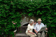 An elderly couple read in the grounds of Danny House, one of England's finest stately homes now maintained as serviced apartments for retired people, bed & breakfast facilities and as a family business. Danny House, Hurstpierspoint, West Sussex