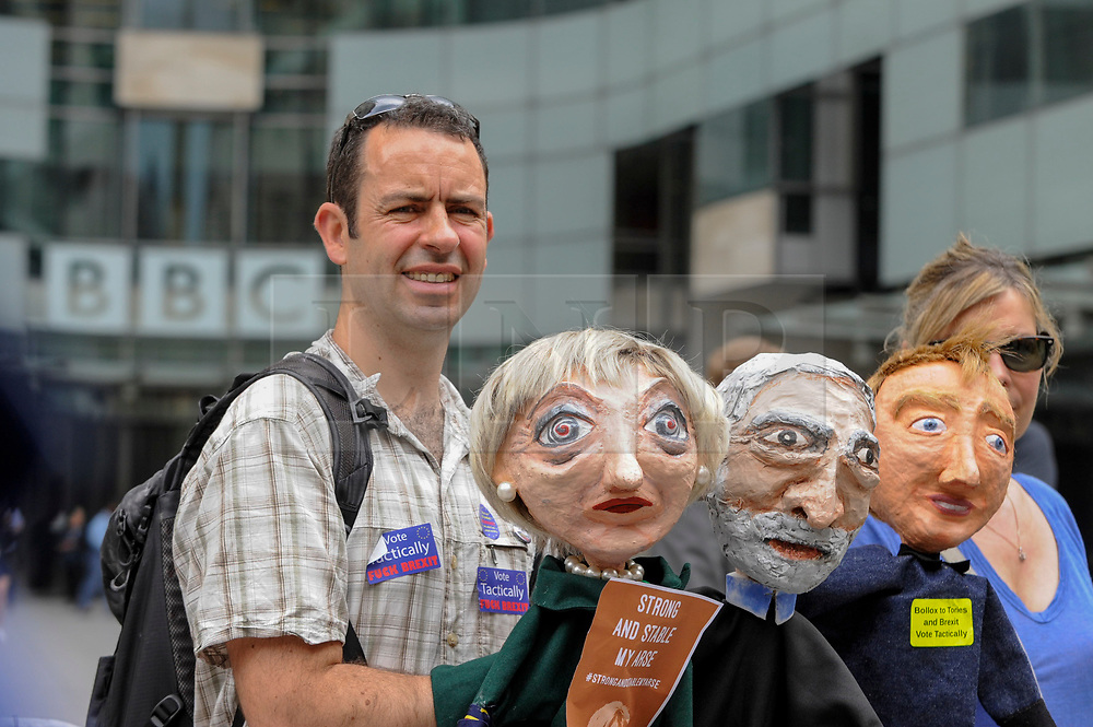 """© Licensed to London News Pictures. 02/06/2017. London, UK. A man carries papier mache puppets depicting Theresa May, Jeremy Corbyn and Tim Farron. Demonstrators gather outside the BBC headquarters in protest against the Corporation for not playing the song """"Liar Liar"""" by Captain Ska on BBC Radio 1.  Organised by The People's Alliance, people carried signs bearing an image of Prime Minister Theresa May with the words """"Liar Liar"""" and """"You Can't Trust Her"""" on each side.   Photo credit : Stephen Chung/LNP"""