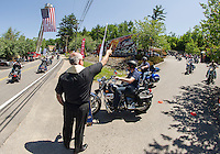 Father Mark Drouin gives a blessing to riders as they leave on the Makris Memorial Ride around Lake Winnipesaukee Saturday morning.  (Karen Bobotas/for the Laconia Daily Sun)