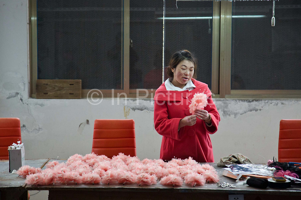 Workers make ornamental flowers at the Yiwu Beautiful Flower Co. Ltd  factory in Yiwu, Zhejiang Province, China on 06 March  2013. The city of Yiwu is known as one of China's largest trading centers for small merchandise and light industry, drawing buyers from around the world. Uncertain global demand, a stronger yuan currency and rising labour costs have taken their toll on Chinese exporters, but analysts believe sales could pick up modestly in 2014 due to improved demand from the United States and Europe.