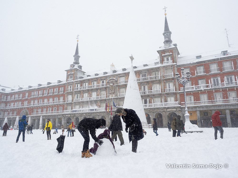 Madrid, Spain. 9 th January, 2021. Three pleople building a snowman at Plaza Mayor square. Storm Filomena hits Madrid (Spain), a weather alert was issued for cold temperatures and heavy snow storms across Spain; according to the weather agency Aemet is expected to be one of the snowiest days in recent years. © Valentin Sama-Rojo.