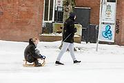In Utrecht trekt een man een jonge vrouw op de slee. Op de achtergrond hangen posters vanwege Corona met de tekst 'Utrecht zorg goed voor elkaar'. Nederland geniet van de eerste sneeuw sinds lange tijd.<br /> <br /> In Utrecht people are sledding. People in the Netherlands enjoy the first snow since years.