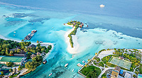 Aerial view of local island Huraa and a nearby resort, North Malé Atoll, Maldives, Indian Ocean with tennis court and boats anchoring in the harbour