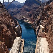 Photo of the rugged terrain at the bottom of the Hoover Dam complex feeding into the lower Colorado River. At bottom of the frame are the twin buildings housing the hydroelectric turbines. At top is the new Mike O'Callaghan – Pat Tillman Memorial Bridge which now handles much of the road traffic over the chasm.