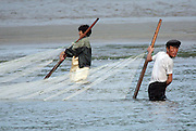 """A North Korean couple pull a fishing net through water in the town of Sinuiju July 8, 2006. China and North Korea are separated by the Yalu River, upon which Chinese tourists take pleaure cruises across the water to  observe their less economically developed neighbors.  North Korea has threatened to take """"stronger physical actions"""" after Japan imposed punitive measures in response to its barrage of missile tests and pushed for international sanctions. North Korea has vowed to carry out more launches and has said it will use force if the international community tries to stop it. DPRK, north korea, china, dandong, border, liaoning, democratic, people's, rebiblic, of, korea, nuclear, test, rice, japan, arms, race, weapons, stalinist, communist, kin jong il"""