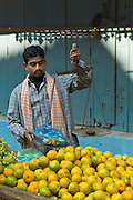 Indian man sells oranges at market stall in alleyway in the city of Varanasi, Benares, Northern India