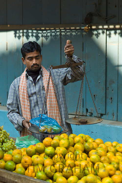 Indian man sells oranges at market stall in alleyway in the city of Varanasi, Benares, Northern India