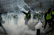 Protester trowing teargas canisters back to the police. More than 125000 gathered in Paris for the Gilets Jaune (Yellow vest) protest. Soon the protest turned violent an protesters clashed with the police, tear gas and flash bombs were fired, many injured and arrested by the police. Paris December 6th 2018. Federico Scoppa