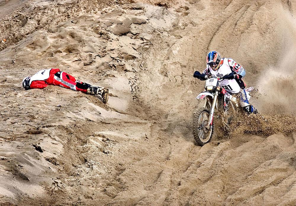 Nederland, Scheveningen, 12-11-2006.<br /> Motorcross.<br /> Gert Heeling passeert de gewonde Dennis de Jong die op het parcours ligt terwijl de race doorgaat. <br /> Honderdvijdtigduizend toeschouwers langs de boulevard zagen vijfhonderd motocrossers van start gaan voor een weergaloze strandrace.<br /> Na vijftien jaar afwezigheid brulden vandaag de motoren weer. Vijfhonderd gespannen motocrossers reden een wedstrijd die nu al tot een van de zwaarste strandraces ter wereld wordt gerekend. <br /> Foto: Klaas Jan van der Weij