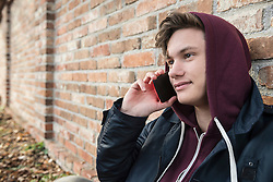 Young man talking on mobile phone and leaning against brick wall, Munich, Bavaria, Germany